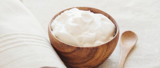 Kokosowy jogurt grecki w drewnianej misce, bez nabiału, bezglutenowy, probiotyczny pokarm dla zdrowia jelit