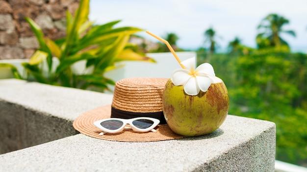 Kokosowy koktajl ozdobiony plumeria, słomkowy kapelusz i okulary przeciwsłoneczne na stole.