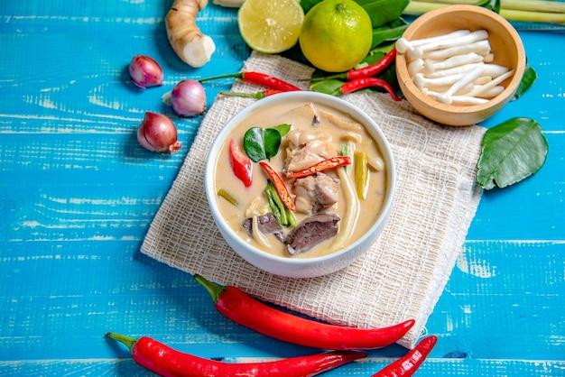 Kokosowy mleko z kurczakiem na błękitnej drewnianej podłoga. tradycyjna tajska zupa