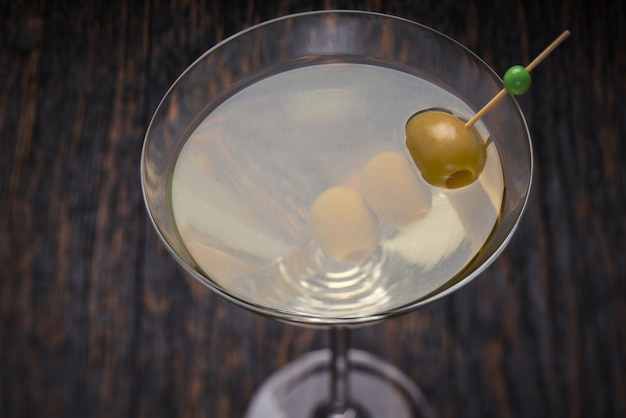 Koktajl alkoholowy na czarnym drewnianym stole. widok z góry.