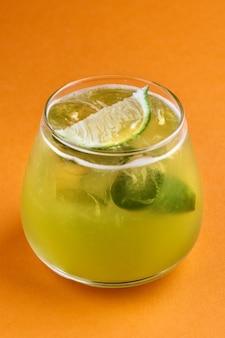 Koktajl alkoholowy smash bazyliowy z zieloną bazylią, na pomarańczowym tle