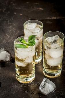 Koktajl alkoholowy wykonany ze złotej tequili z kostkami lodu i miętą. na czarnym betonowym stole. skopiuj s
