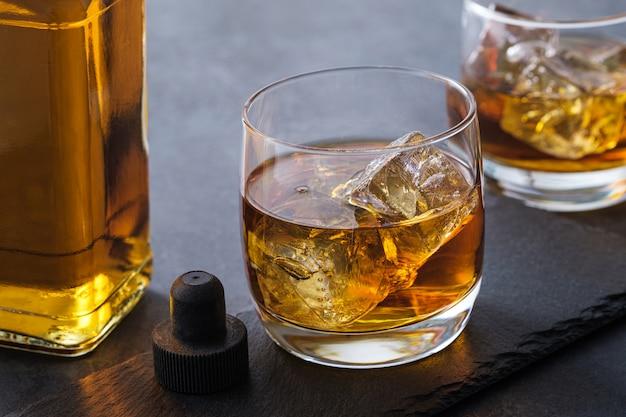 Koktajl alkoholowy z kostkami lodu. whisky lub bourbon na ciemnym tle kamienia