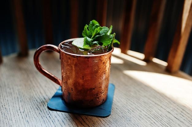 Koktajl alkoholowy z lodem, miętą i limonką w brązowej filiżance na stole barowym