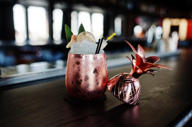 Koktajl alkoholowy z lodem w brązowym szkle na stole barowym
