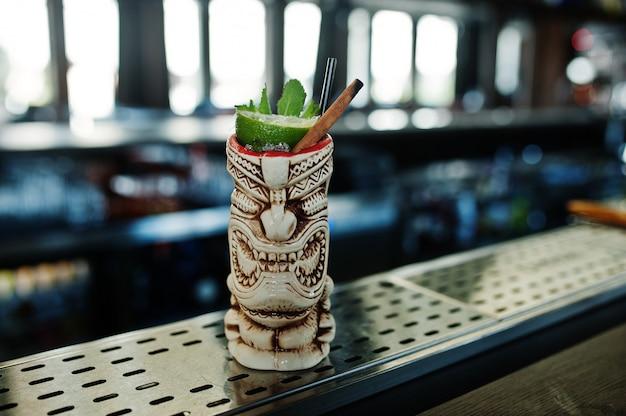Koktajl alkoholowy z miętą i limonką w oryginalnie glinianym kieliszku voodoo na stole barowym