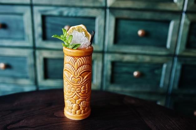 Koktajl alkoholowy z miętą w oryginalnie glinianym szkle na stole barowym