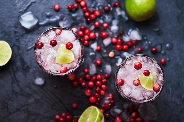 Koktajl alkoholowy z wódką, sokiem żurawinowym i lodem. dwa koktajle cape codder w szklankach casablanca, przybrane limonką i świeżą żurawiną. widok z góry.