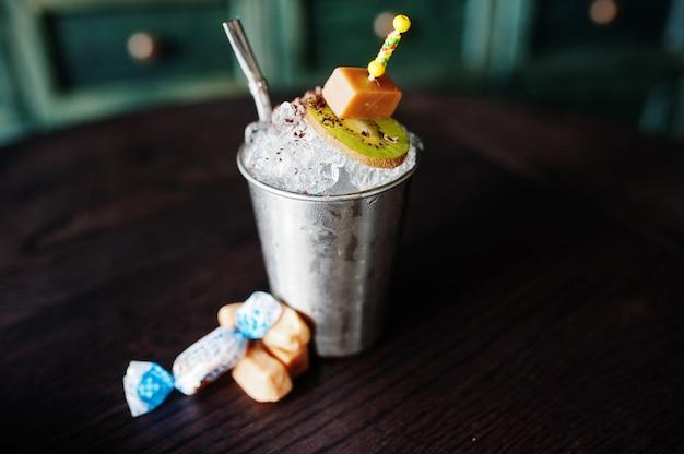 Koktajl alkoholowy ze słodyczami i cukierkami w małym srebrnym wiaderku przy stole barowym