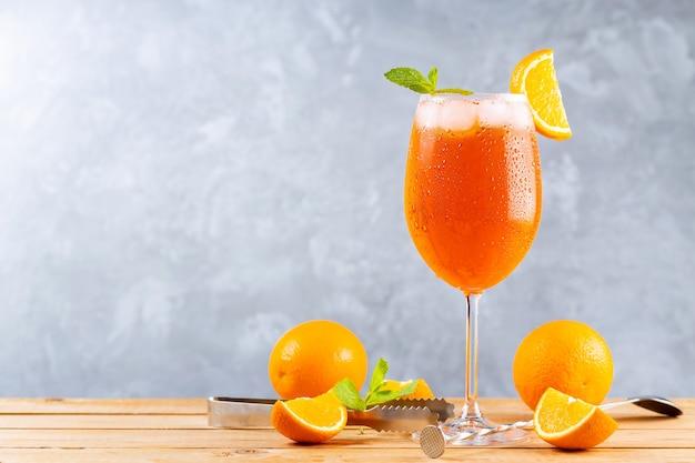 Koktajl aperol spritz z akcesoriami barowymi. włoski aperol spritz koktajl i plasterki pomarańczy na szarym tle. spitz z aperolem koktajlowym ze świeżą miętą