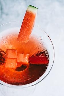 Koktajl arbuzowy w kieliszku martini na stole. orzeźwiający napój