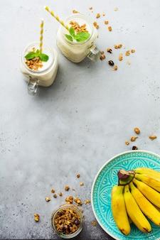Koktajl bananowy z muesli, bakaliami i miętą na szarym tle betonu.