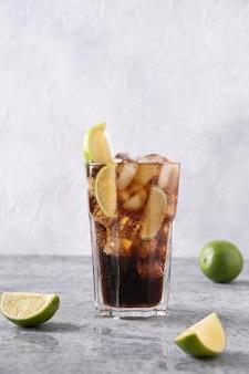 Koktajl cuba libre lub mrożona herbata z długiej wyspy z romem, colą, limonką i lodem w szkle na szarym kamiennym stole.