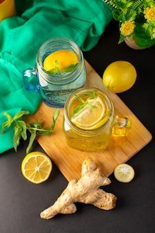 Koktajl cytrynowy z widokiem z góry świeży chłodny napój wewnątrz szklanych kubków pokrojone w plasterki i całe cytryny wraz z kwiatami na ciemnym tle napój koktajlowy owoc