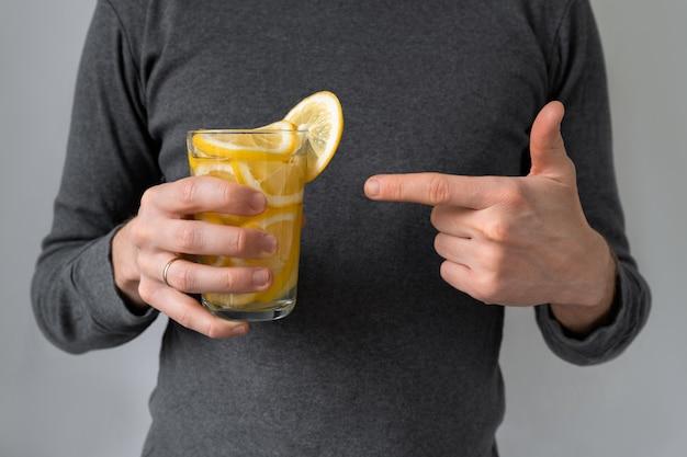 Koktajl cytrynowy z witaminą c. ręka mężczyzny trzyma szklankę wody z cytryną w dłoniach. wstrząsowa dawka witaminy c podczas pandemii.