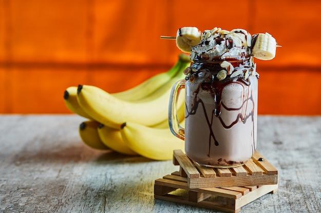 Koktajl czekoladowy z syropem czekoladowym i gałązką bananów