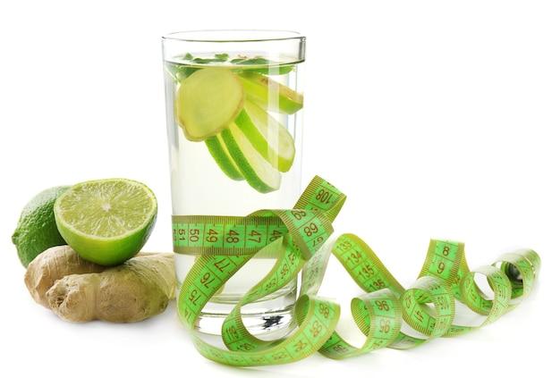 Koktajl dietetyczny z plasterkami cytryny i centymetrem na stole i białej powierzchni