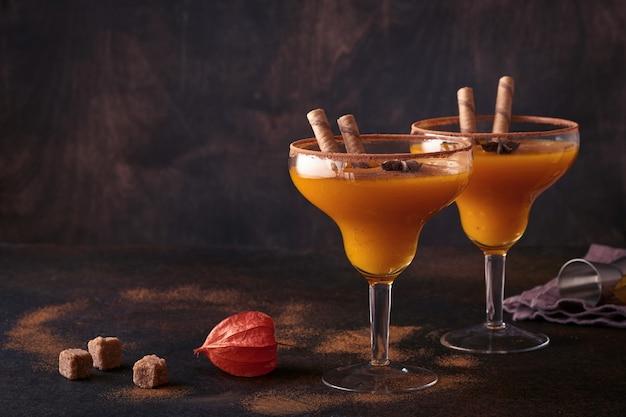 Koktajl dyniowy z cynamonem, sokiem pomarańczowym i kakao w szklanych kubkach. dynia jesień napój na halloween lub święto dziękczynienia.