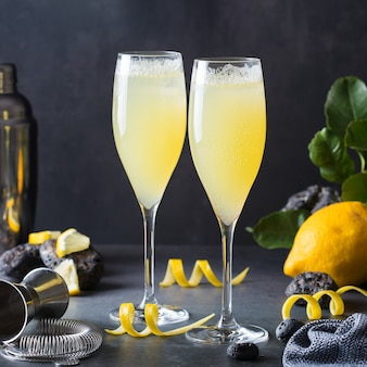 Koktajl francuski 75 z twardym seltzerem cytrynowym zamiast szampana. letni napój orzeźwiający, napój na stole z akcesoriami barmana do miksologii