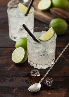 Koktajl gimlet kamikaze w kryształowych kieliszkach z plasterkiem limonki i lodem na drewnianej powierzchni ze świeżymi limonkami i łyżką.