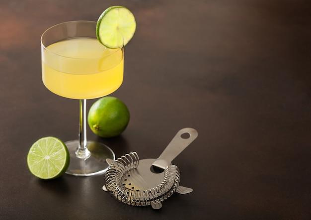 Koktajl gimlet kamikaze w nowoczesnym szkle z brązową powierzchnią plasterka limonki ze świeżymi limonkami i sitkiem. widok z góry
