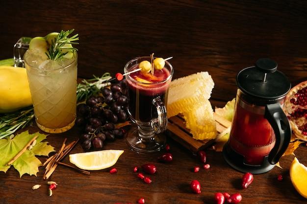 Koktajl jabłkowy z rozmarynem, grzanym winem z jagodami, cytryną, miodem i herbatą z granatu w french press na stole w restauracji