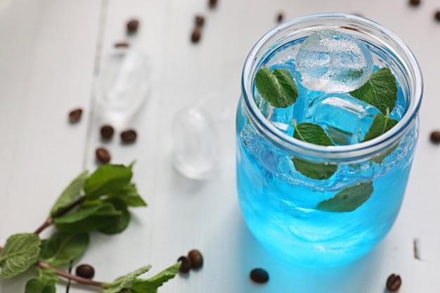 Koktajl jest niebieski w słoiku z miętą i lodem. obraz z głębią ostrości.