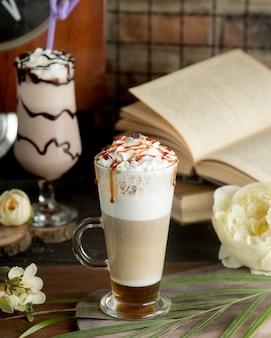 Koktajl kawowy z mlekiem i bitą śmietaną w szklance.