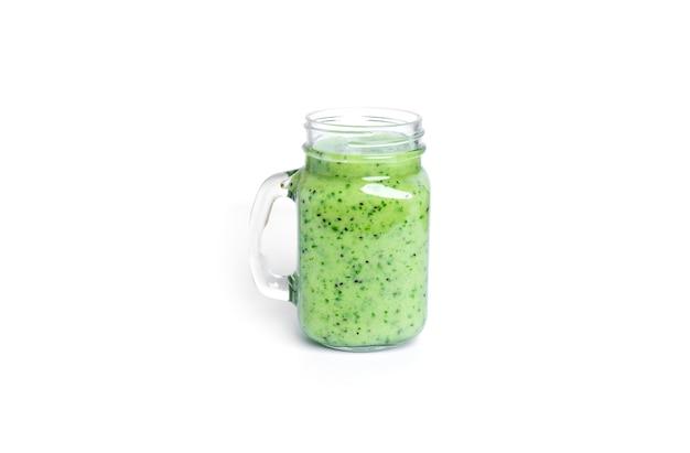 Koktajl kiwi i szpinaku na białym tle. słoik z zielonym smoothie.