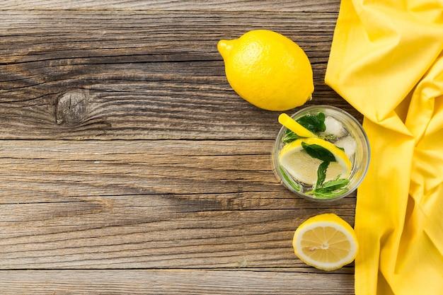 Koktajl lemoniadowy lub mojito z cytryną i miętą z lodem. zimny letni orzeźwiający napój ozdobiony żółtą serwetką na drewnianym stole. widok z góry z miejscem na kopię