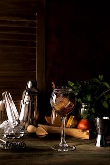 Koktajl letni z cynamonem, jagodami i lodem na ciemnym drewnianym backgorund