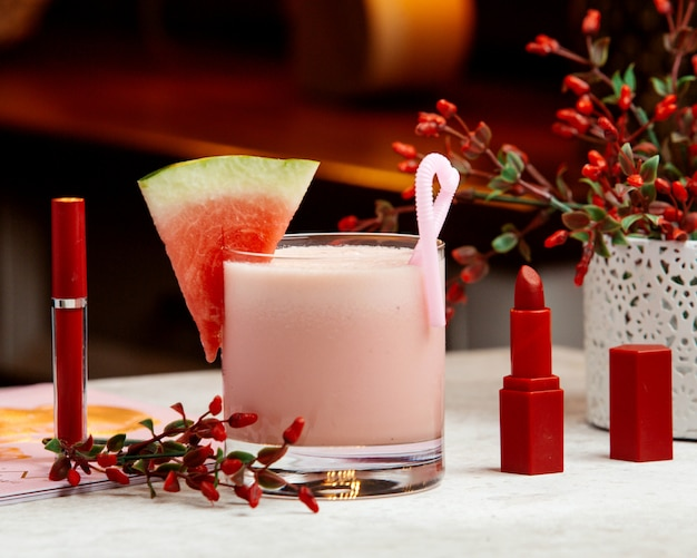 Koktajl mleczny z arbuza przyozdobiony arbuzem, obok czerwonej szminki