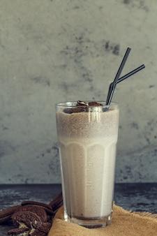 Koktajl mleczny z ciasteczkami w wysokiej szklance.
