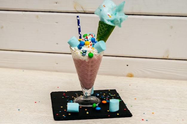 Koktajl mleczny z cukierkami marshmallow lub freak shake z bitą śmietaną i innymi smakołykami.