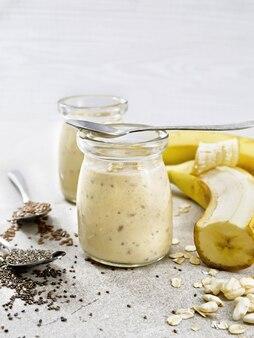 Koktajl mleczny z nasionami chia, nasionami lnu, płatkami owsianymi, ryżem dmuchanym i bananem w dwóch szklanych słoikach na tle kamiennego stołu