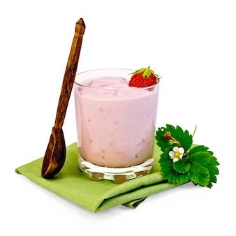 Koktajl mleczny z truskawkami w szklance, drewnianą łyżką, kwiat truskawki z liśćmi na serwetce na białym tle