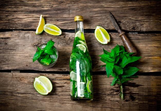 Koktajl mojito. limonka, mięta, nóż, przygotowuje się również koktajl w butelce i kieliszku. widok z góry