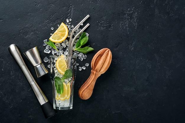 Koktajl mojito lub lemoniada w szklance typu highball z miętą w kostkach lodu.