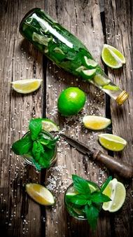 Koktajl mojito . składniki na koktajl - limonki, mięta, nóż, jest również przygotowany koktajl w butelce i kieliszku. widok z góry