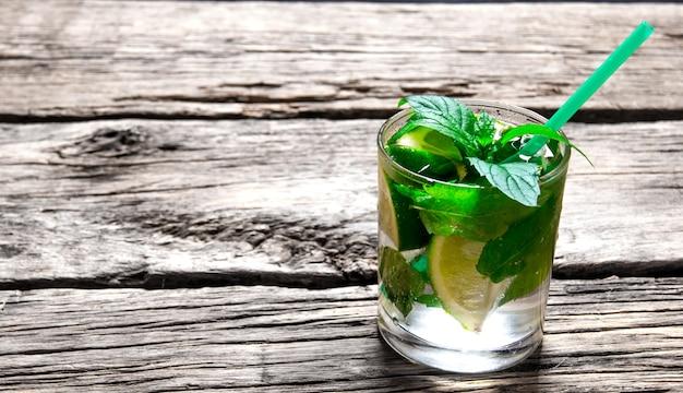Koktajl mojito . świeżo przygotowane mojito w szklance z dodatkiem mięty, limonki i rumu. na drewnianym stole.
