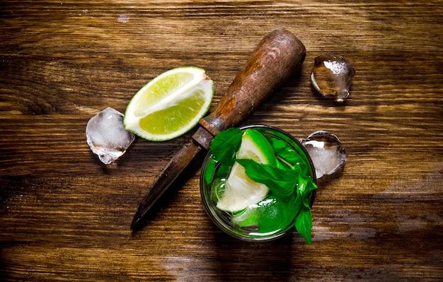 Koktajl mojito. szklanka fajnego koktajlu, lodu, noża i plasterków limonki na drewnianym stole. widok z góry