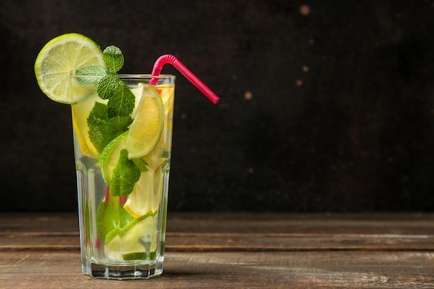 Koktajl mojito w szklance z limonką, miętą i cytryną na drewnianym brązowym stole