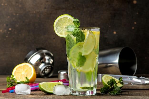 Koktajl mojito w szklance z limonką, miętą i cytryną oraz akcesoria barowe na drewnianym brązowym stole. gotowanie mojito.