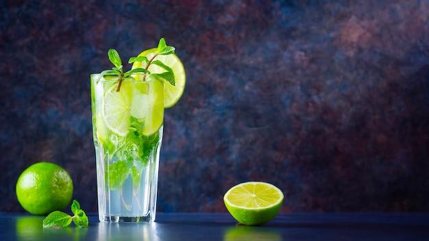 Koktajl mojito z limonką i miętą w wysokim kieliszku. świeże mojito w szkle na ciemnym tle. orzeźwiający koktajl miętowy z limonką. wlewana woda. skopiuj miejsce