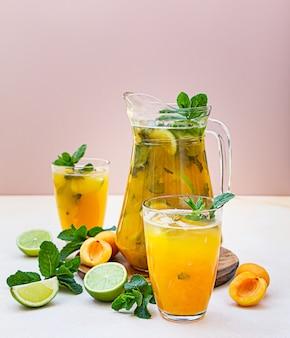 Koktajl morelowy lub mrożona herbata ze świeżą miętą, limonką i morelami. letni orzeźwiający zimny napój.