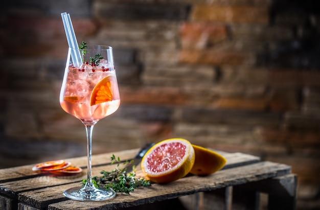 Koktajl na starej drewnianej desce napój alkoholowy z tropikalnymi owocami, czerwoną papryką i ziołami