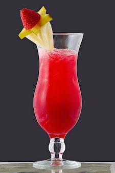 Koktajl owocowy w szklanej misce na szarym tle.