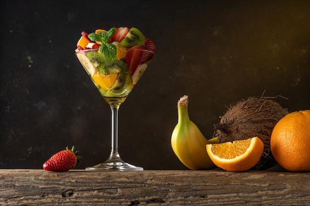 Koktajl owocowy w szkle martini na drewnianym stole.