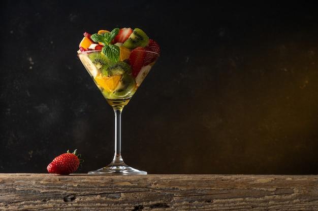 Koktajl owocowy w szkle martini na drewnianym stole