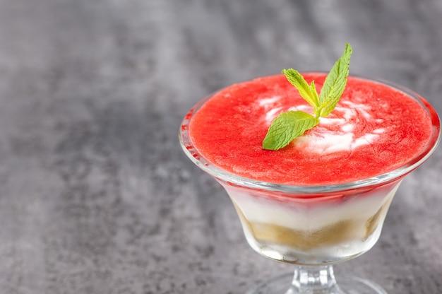 Koktajl owocowy z płatkiem w szklanym wazonie na szarej powierzchni.